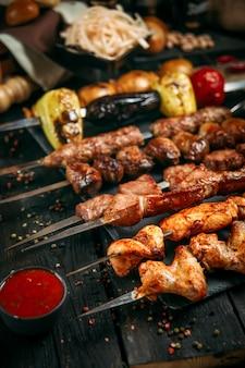 Gruziński zestaw szaszłyków kebabowych na ciemnej drewnianej powierzchni