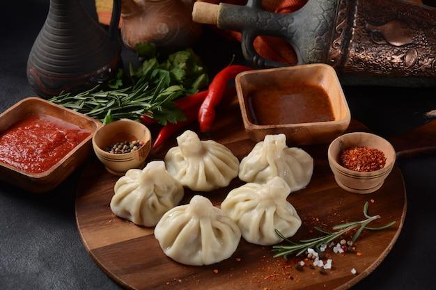Gruzińskie pierożki chinkali z mięsem i czerwoną papryką, tradycyjna narodowa kuchnia gruzińska. chinkali z lokalnymi sosami - tkemali, satsebeli, adzhika.