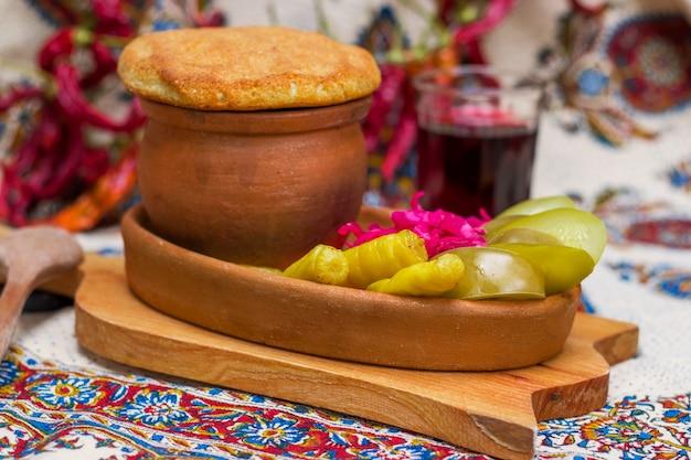 Gruzińskie tradycyjne jedzenie lobio lub zupa fasolowa z nerkami i fasolą szparagową z zebranymi warzywami i czerwonym winem. tbilisi, gruzja.