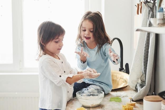 Gry dla dzieci. przyjaciele z przedszkola uczą się gotować z mąki w białej kuchni.