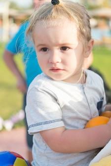 Gry i rozrywka dla dzieci. dziecko dziecko trzymać piłkę. ładny chłopak chce się dobrze bawić z bliska. chłopiec dziecko grać w piłkę na zewnątrz. maluch na wakacjach potrzebuje rozrywki. najlepsze zajęcia dla malucha.