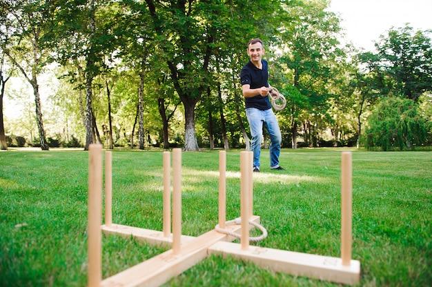 Gry na świeżym powietrzu, facet gra w rzutki w parku.