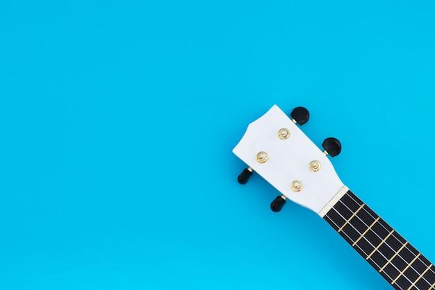Gryf ukulele na niebieskim tle. lay lay. miejsce na tekst