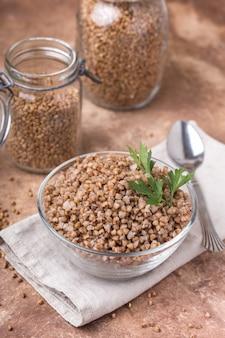 Gryka gotowana w szklance, miska przezroczysta, liść pietruszki, serwetka lniana, słoiki do przechowywania zbóż, tło brązowe, zdrowotne, pionowe
