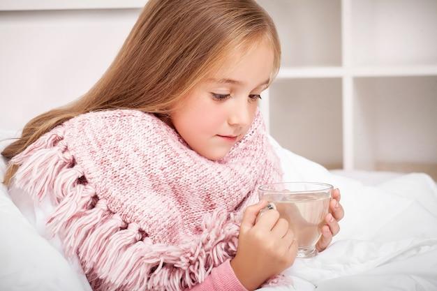 Grypa. chora mała dziewczynka z gorącą herbatą cytrynową