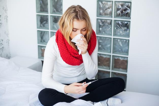Grypa, kobieta cierpi na zimno leżąc w łóżku