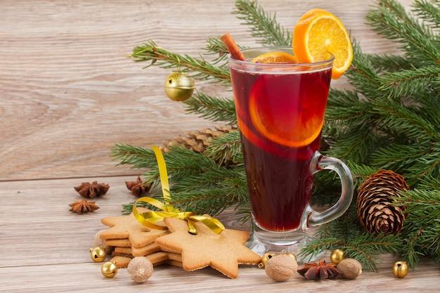 Grzane czerwone wino z bożonarodzeniową wiecznie zieloną jodłą na drewnianym tle
