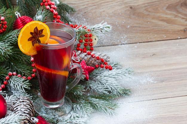 Grzane czerwone wino z dekorowaną choinką w śniegu na drewnianym tle