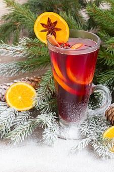 Grzane czerwone wino ze świeżym bożonarodzeniowym wiecznie zielonym drzewem w śniegu na drewnianym tle