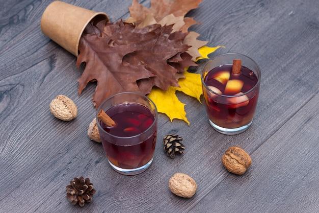 Grzane wino czerwone z przyprawami i owocami na drewnianym stole. jesienne liście jesienią.