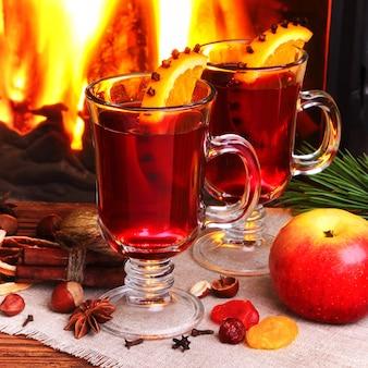 Grzane wino - dwie szklanki na tle płonącego kominka