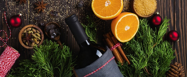 Grzane wino gorący napój z cytrusami, jabłkiem, granatem i przyprawami w aluminiowej zapiekance z zabytkowymi zabawkami choinkowymi i gałązką jodły na betonowym tle. selektywne skupienie.