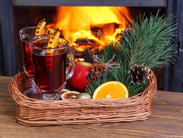 Grzane wino na wiklinowej tacy na tle płonącego kominka