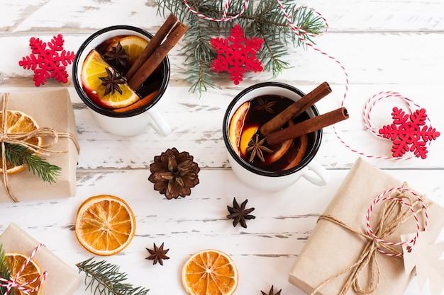 Grzane wino w białych emaliowanych kubkach z przyprawami i owocami cytrusowymi na drewnianym stole z futrzanymi gałęziami i prezentami świątecznymi.