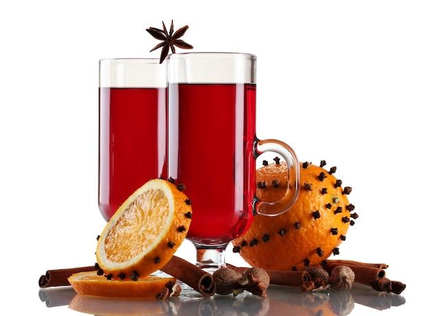 Grzane wino w kieliszku, przyprawa i pomarańcza na białym tle