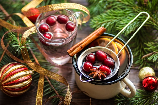 Grzane wino w metalowym kubku z jagodami, laskami cynamonu i anyżem na brązowym drewnianym stole