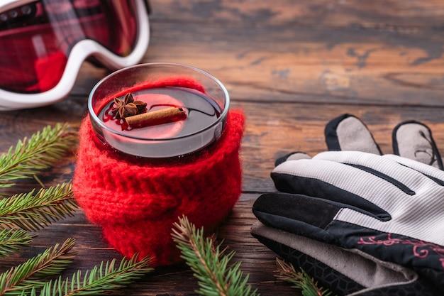 Grzane wino w ręce kobiety przytulne domowe koncepcja składników zimowe okulary sportowe rękawice narciarskie
