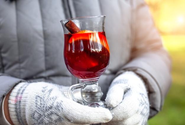 Grzane wino w szklance grzane wino jesienne mandarynki gluhwein w dłoniach kobiety w rękawiczkach