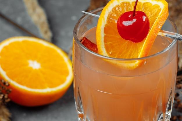 Grzane wino w szklanych kieliszkach z jabłkami pomarańczy i cynamonem. gorący świąteczny napój na szaro