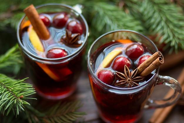 Grzane wino w szklanym kubku z jagodami, laskami cynamonu i anyżem na brązowym drewnianym stole