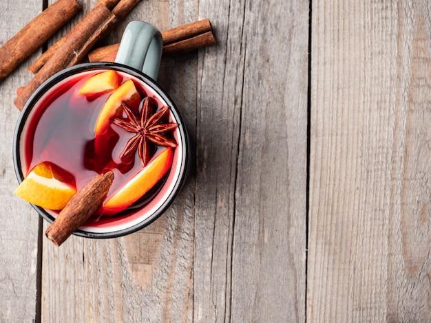 Grzane wino z cynamonem i anyżem na drewnianym stole.