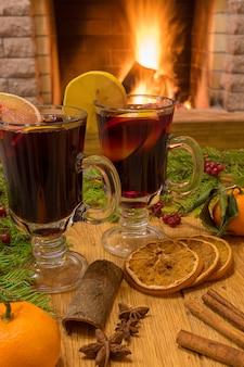 Grzane wino z glintwine w szkłach i dekoracje świąteczne, przy przytulnym kominku