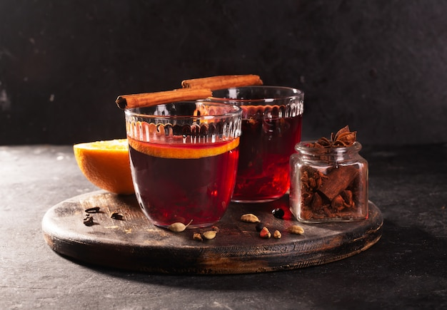 Grzane wino z plasterkiem pomarańczy i przypraw na tle drewnianych, z bliska