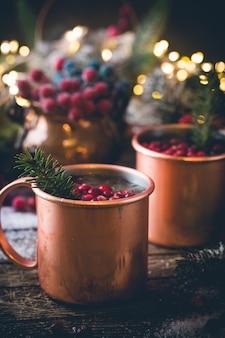 Grzane wino z żurawiną w miedzianym kubku ze świątecznymi dekoracjami na drewnianym stole