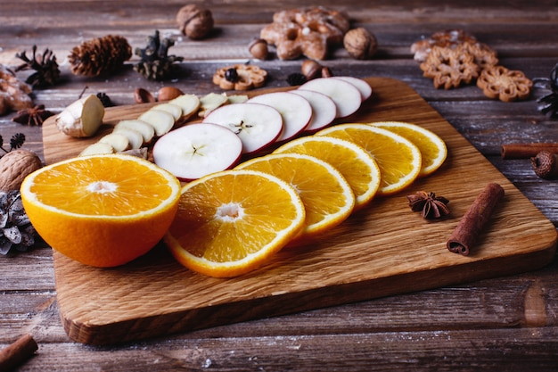 Grzaniec z wina. pomarańcze, jabłka i gatunki leżą na drewnianym stole