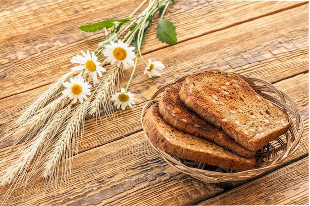 Grzanki w wiklinowym koszu, kwiaty rumianku i suche kłosy pszenicy na drewnianych deskach. widok z góry.