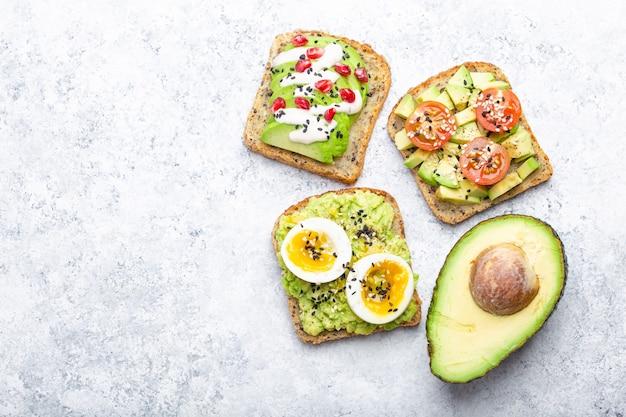Grzanki z awokado z jajkiem, pomidorami, przyprawami i połową całego awokado na białym tle kamienia, miejsca na tekst. zdrowe śniadaniowe kanapki z awokado z różnymi dodatkami, widok z góry, zbliżenie