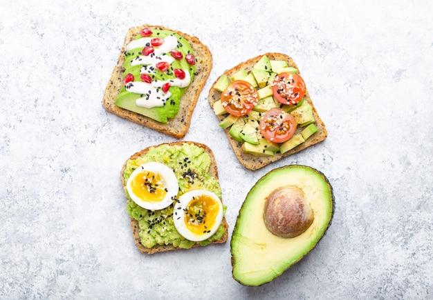 Grzanki z awokado z jajkiem, pomidorami, przyprawami i połową całego awokado na białym tle kamienia. zdrowe śniadaniowe kanapki z awokado z różnymi dodatkami, widok z góry, zbliżenie