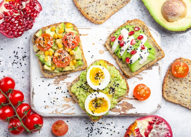 Grzanki z awokado z jajkiem, pomidorami, przyprawami na białej drewnianej rustykalnej desce do krojenia, kamienne tło. składniki na zdrowe śniadaniowe kanapki z awokado z różnymi dodatkami, widok z góry, zbliżenie