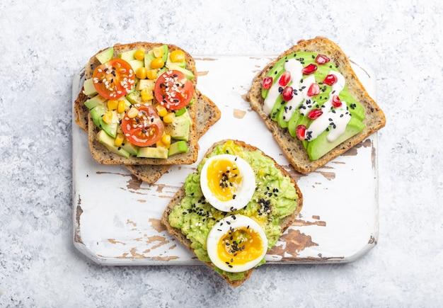 Grzanki z awokado z jajkiem, pomidorami, przyprawami na białym drewnianym rustykalnym krojenia na tle kamienia. robienie zdrowych kanapek śniadaniowych z awokado z różnymi dodatkami, widok z góry, zbliżenie