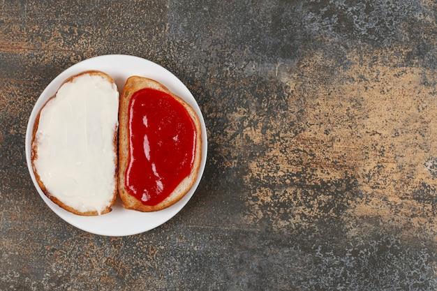 Grzanki z dżemem truskawkowym i śmietaną na białym talerzu.