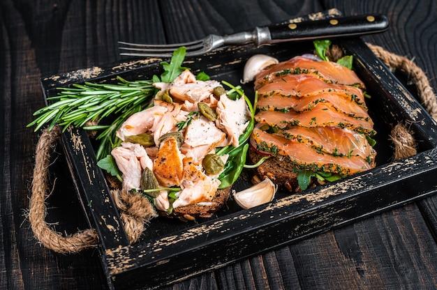 Grzanki z łososiem wędzonym na ciepło i na zimno, rukolą na drewnianej tacy z ziołami. czarne tło drewniane. widok z góry.