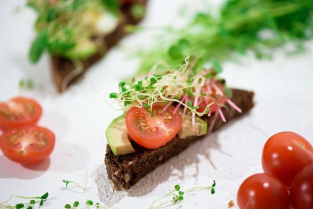 Grzanki z mikrozielonymi. ręka trzyma zdrowy toast. koncepcja zdrowej żywności. super jedzenie.
