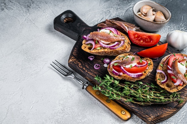 Grzanki z oliwą, ziołami, pomidorami i pikantnymi filetami z anchois. biały stół. widok z góry. skopiuj miejsce.