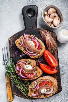 Grzanki z oliwą, ziołami, pomidorami i pikantnymi filetami z anchois