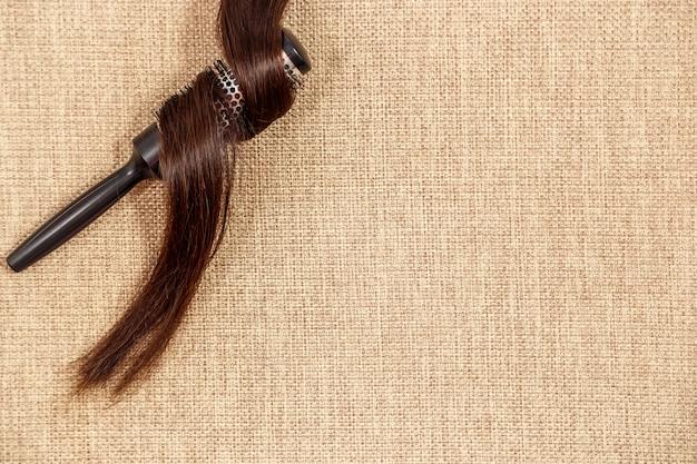 Grzebień z ciemnym włosy na beżowym tle odgórny widok