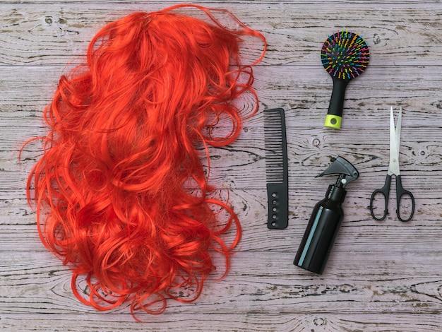 Grzebienie, nożyczki, spray i peruka na drewnianym stole. akcesoria do tworzenia stylizacji i pielęgnacji włosów.