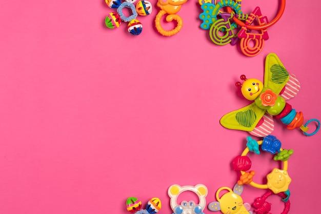 Grzechotka dla dzieci z plastiku na różowym tle. widok z góry. skopiuj miejsce. płaskie ułożenie