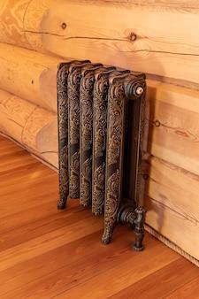 Grzejnik kuty w stylu retro w pokoju z bali drewnianych, wnętrze pokoju, podłoga i ściana drewniana, instalacja co, ciepły dom.
