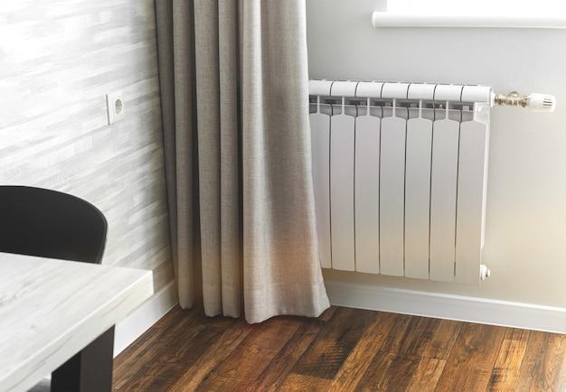 Grzejny grzejnik metalowy, biały grzejnik w nowoczesnym wnętrzu mieszkania z drewnianą podłogą