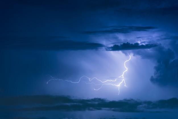 Grzmot burzy uderzenie pioruna na ciemnym tle pochmurnego nieba w nocy.