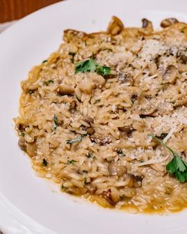 Grzybowe risotto przyozdobione pionowym startym parmezanem i natką pietruszki