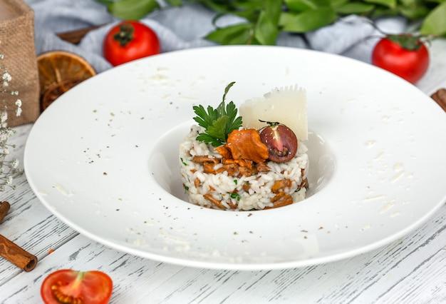Grzybowe risotto z grzybami przyozdobione parmezanem i natką pietruszki