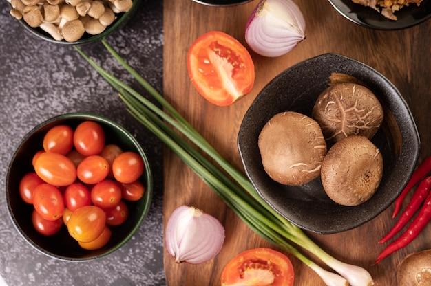 Grzyby shiitake z czosnkiem, pomidorem, papryką, szczypiorkiem i czerwoną cebulą na podłodze z czarnego cementu.