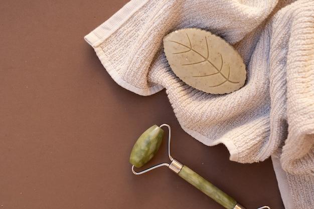 Gua sha, wałek do masażu twarzy wykonany z kamienia naturalnego, koncepcja domowego spa, tło w kolorach ziemi