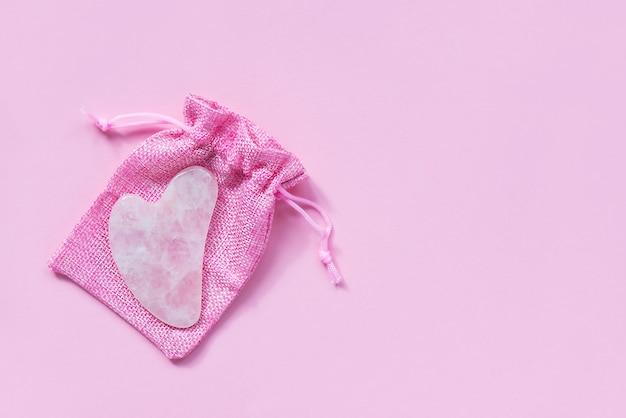 Gua sha z różowego kwarcu na różowej torbie
